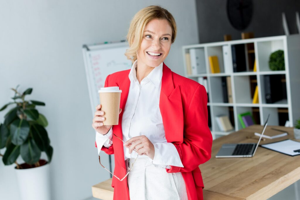 attractive businesswoman standing with coffee in paper cup in office